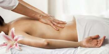 Masseuse giving a relaxing back massage at a spa. You may also like: